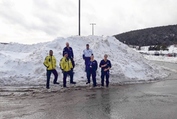 Security Guards Standing on Snow Pile